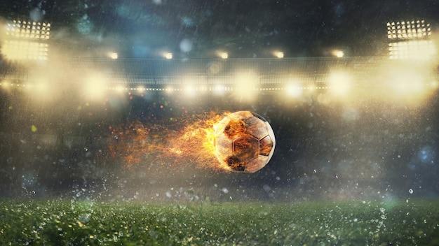 Close de uma bola de futebol em chamas chutada com força no estádio