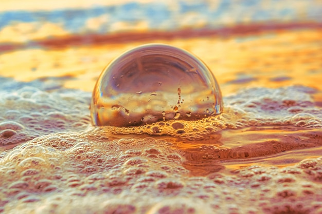 Close de uma bola transparente na areia cercada pelo mar durante o pôr do sol à noite