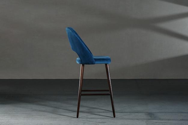 Close de uma cadeira azul com pernas altas em uma sala com paredes cinza