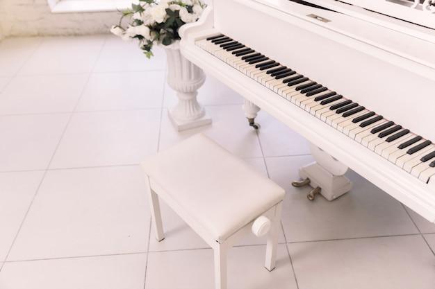 Close de uma cadeira perto do piano.