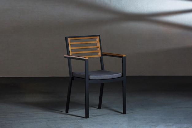 Close de uma cadeira simples e moderna com pernas metálicas em uma sala com paredes cinza