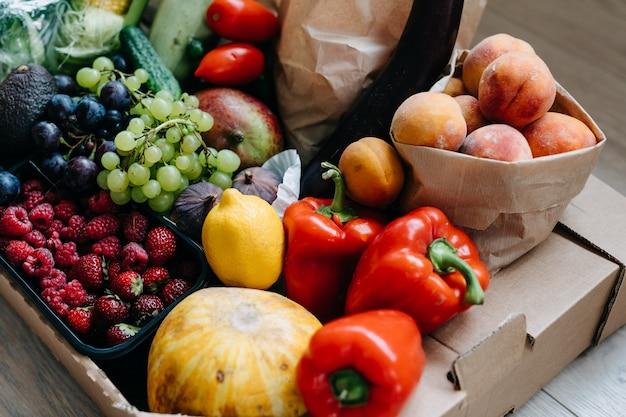 Close de uma caixa cheia de vários vegetais orgânicos frescos, frutas e bagas conceito de entrega de comida