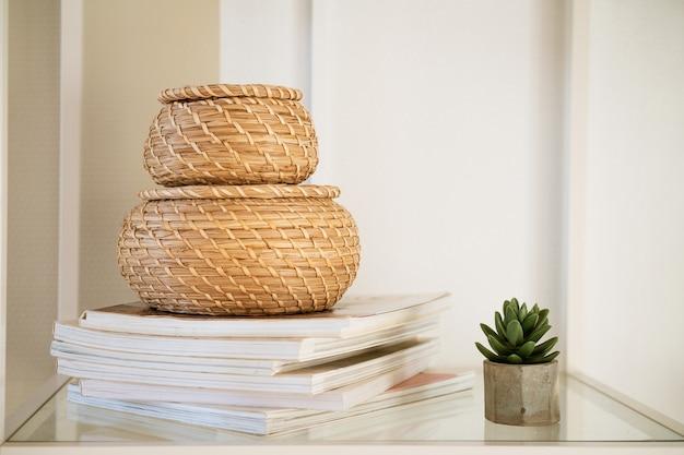 Close de uma caixa de palha redonda com uma tampa em uma prateleira branca de itens ecologicamente corretos para armazenar pequenos ...
