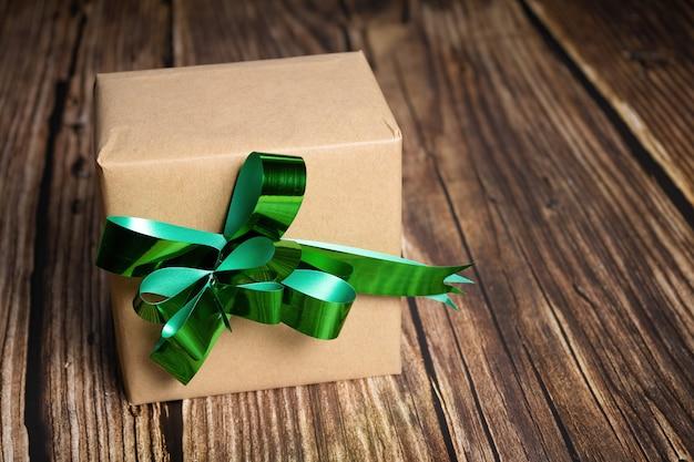 Close de uma caixa de presente com uma fita verde em fundo de madeira
