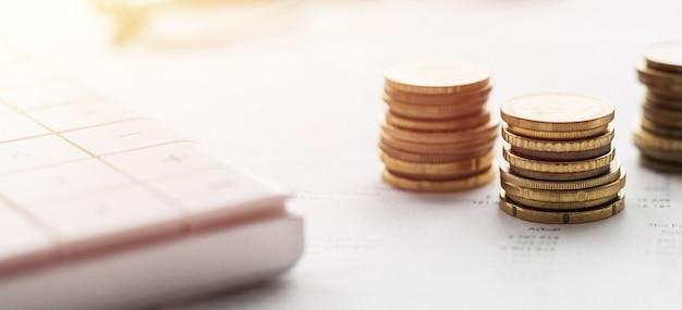 Close de uma calculadora e moedas em uma parede de dados financeiros