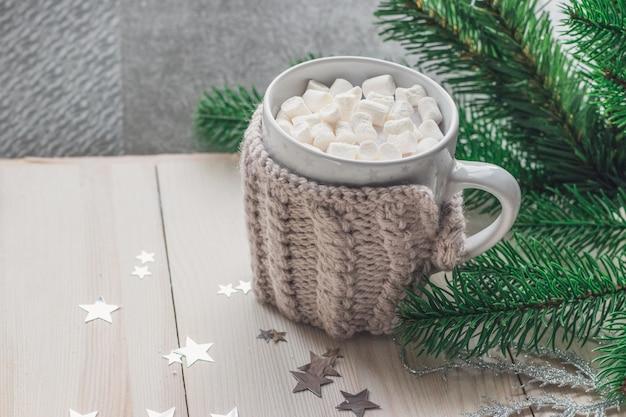 Close de uma caneca fofa cheia de marshmallows cercada por enfeites de natal na mesa