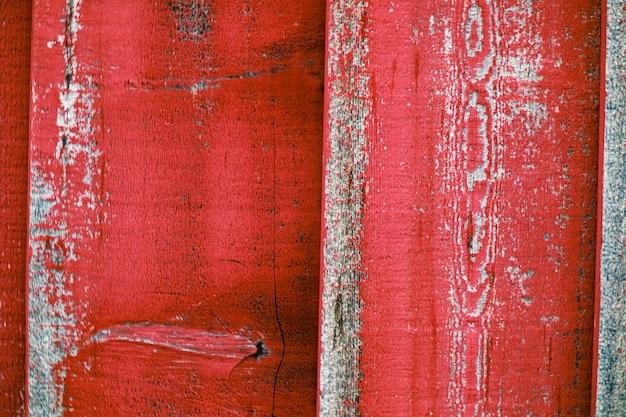 Close de uma cerca de madeira pintada de vermelho