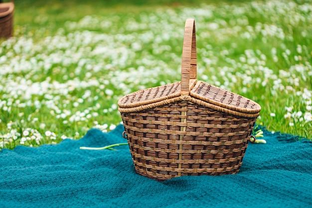Close de uma cesta de piquenique em um pano azul cercado por flores brancas