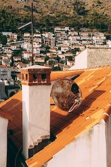 Close de uma chaminé e antenas parabólicas nas telhas laranja de uma casa