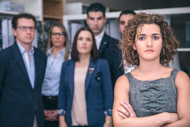 Close de uma chefe executiva em pé na sede com sua equipe em segundo plano