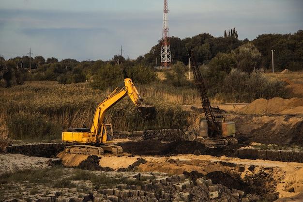 Close de uma construção em andamento com trilhos e uma escavadeira em um terreno abandonado