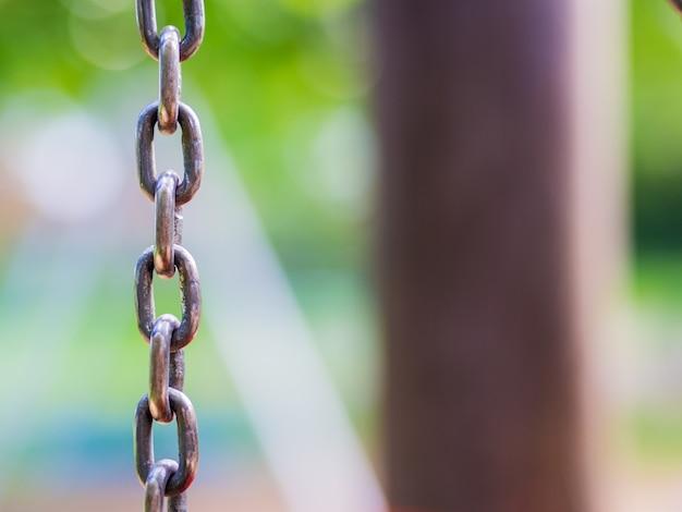 Close de uma corrente de balanço de metal cinza em um playground