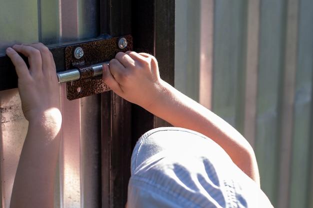Close de uma criança abrindo o portão de ferro