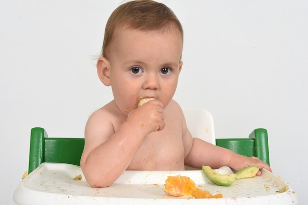 Close de uma criança comendo banana no fundo branco