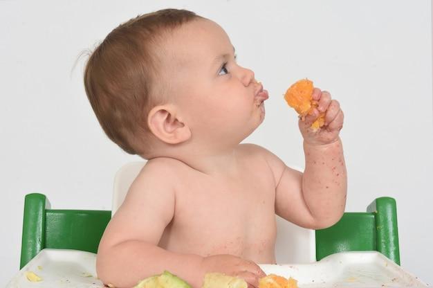 Close de uma criança comendo uma fruta laranja em fundo branco