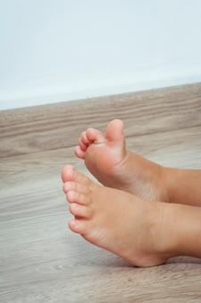 Close de uma criança descalça no chão