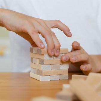 Close de uma criança jogando um jogo de torre de madeira