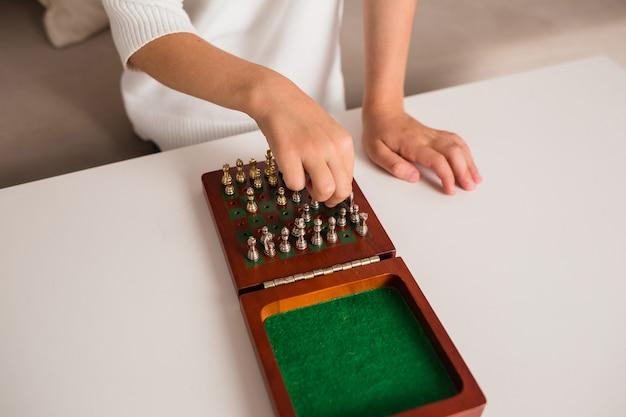 Close de uma criança jogando xadrez em uma mesa