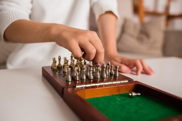 Close de uma criança jogando xadrez em uma sala