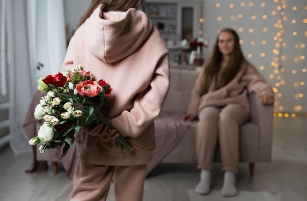 Close de uma criança segurando um buquê de flores para a mãe