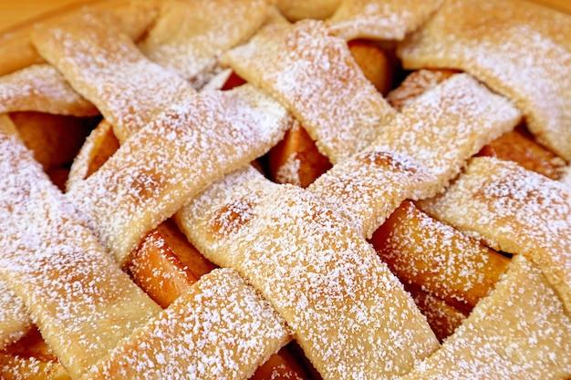 Close de uma crosta de torta de maçã caseira de treliça tecida polvilhada com açúcar em pó