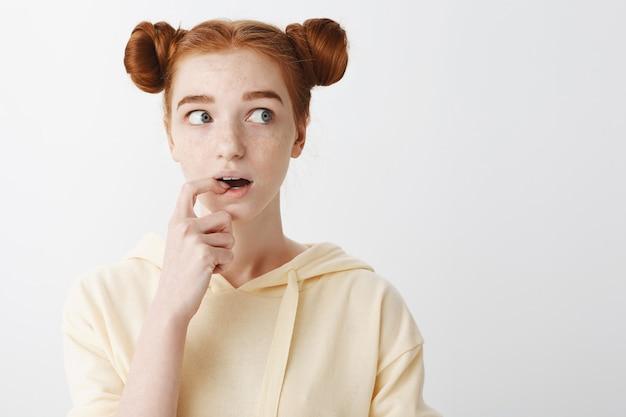 Close de uma curiosa e fofa adolescente ruiva parecendo interessada
