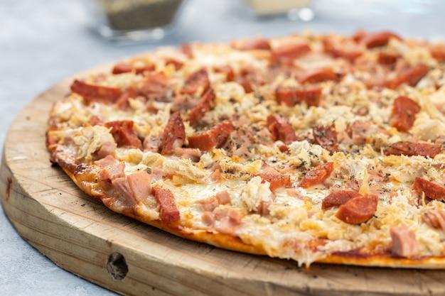 Close de uma deliciosa pizza com linguiça fatiada e queijo derretido em uma placa sob as luzes