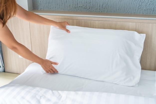 Close de uma empregada doméstica fazendo cama em um quarto de hotel