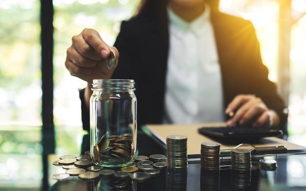 Close de uma empresária colocando moedas em uma jarra de vidro, cálculo e empilhamento de dinheiro para salvar e conceito financeiro