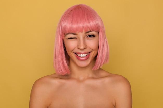 Close de uma encantadora jovem alegre de cabelos rosa com corte de cabelo curto na moda, posando sobre uma parede de mostarda, olhando divertidamente para a câmera e dando uma piscadela