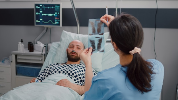 Close de uma enfermeira mostrando radiografia de ossos monitorando a recuperação de doenças