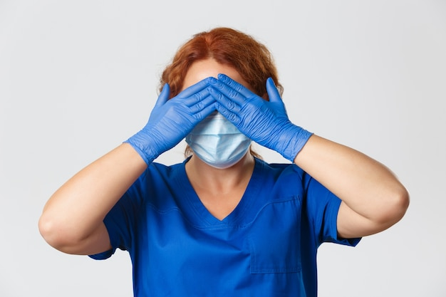 Close de uma enfermeira ou médica com máscara facial, luvas de borracha e esfrega fecha os olhos com as mãos, antecipando, em pé com os olhos vendados