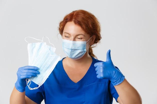 Close de uma enfermeira profissional, o médico recomenda o uso de máscaras e equipamentos de proteção para evitar o surto de vírus, polegar para cima