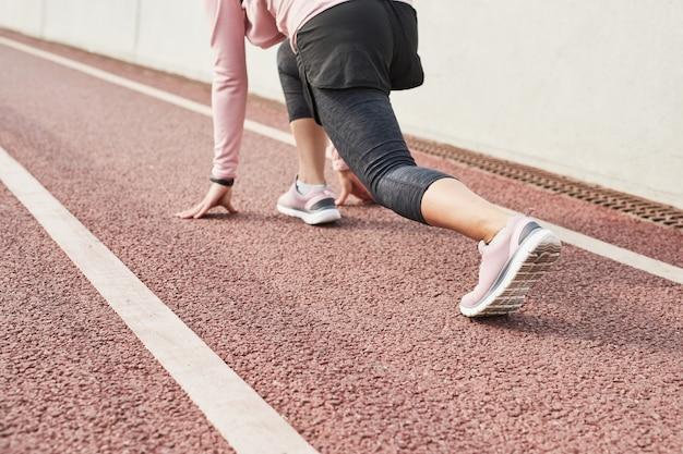 Close de uma esportista em roupas esportivas, em pé na pose e pronta para correr no estádio