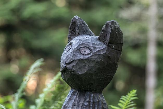 Close de uma estátua de gato preto de madeira em um campo sob a luz do sol com um fundo desfocado