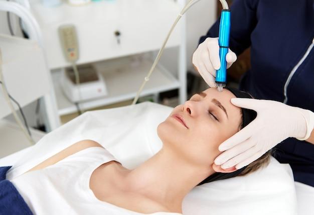 Close de uma esteticista usando um peeling aqua para limpar e esfoliar o rosto de uma mulher. remoção de escórias de pele nos poros com equipamento especial em cosmetologia de hardware.