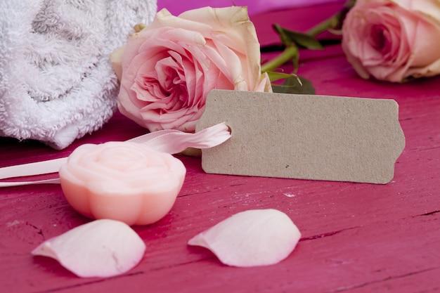 Close de uma etiqueta, lindas rosas cor de rosa e uma vela em uma superfície cor de rosa