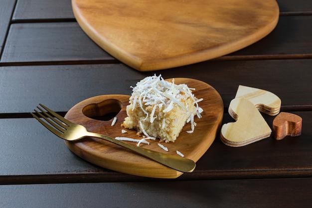 Close de uma fatia de bolo de coco em uma placa de madeira em forma de coração.