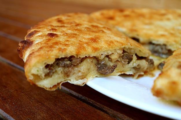 Close de uma fatia de kubdari, saboroso pão achatado georgiano recheado com carne temperada