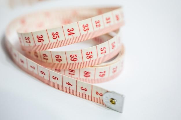 Close de uma fita métrica branca e vermelha na mesa sob as luzes