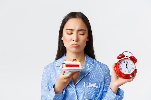 Close de uma fofa garota asiática de pijama chateada, mostrando o relógio e olhando com pesar