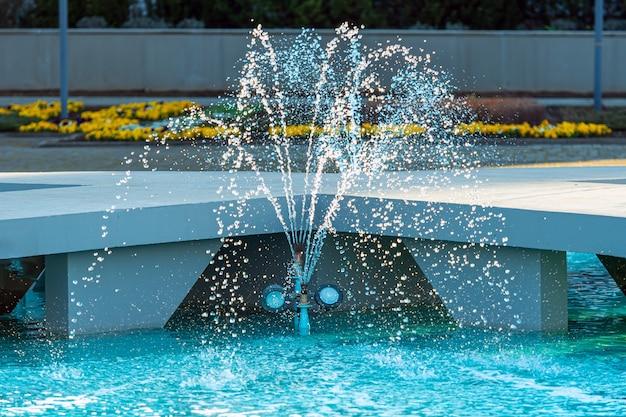 Close de uma fonte externa e uma piscina com água azul límpida