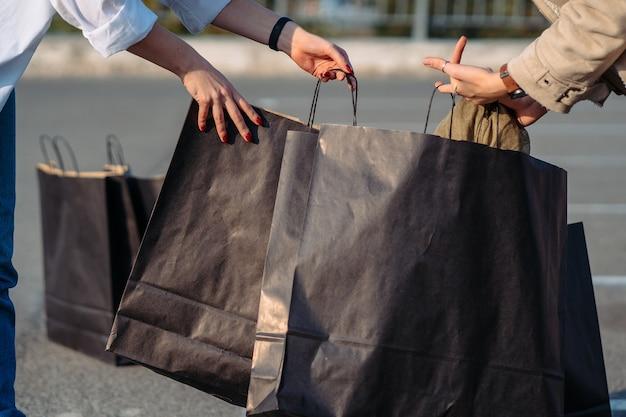 Close de uma garota abre a sacola de compras e está considerando suas compras.