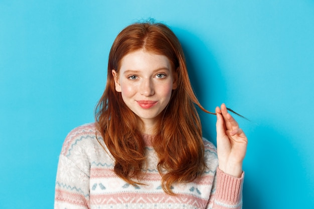 Close de uma garota adolescente ruiva confiante e atrevida olhando para a câmera, brincando com uma mecha de cabelo e sorrindo, em pé sobre um fundo azul