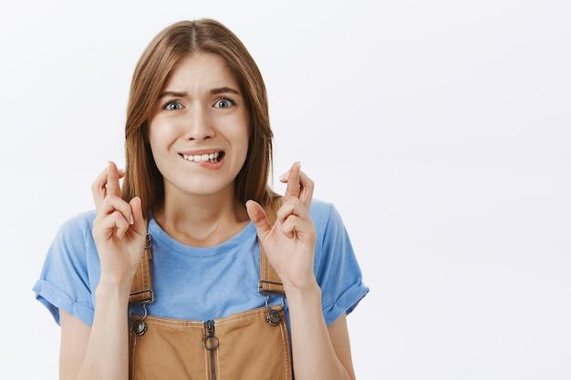 Close de uma garota ansiosa e preocupada orando, cruze os dedos, boa sorte