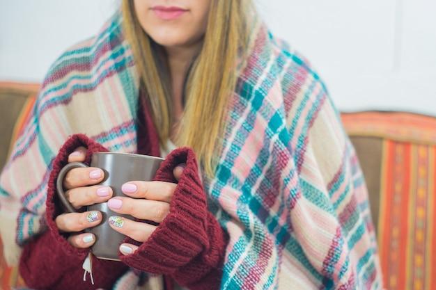 Close de uma garota coberta com um lenço segurando uma caneca
