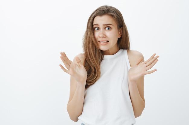 Close de uma garota indecisa e preocupada dando de ombros e levantando as mãos com uma careta confusa