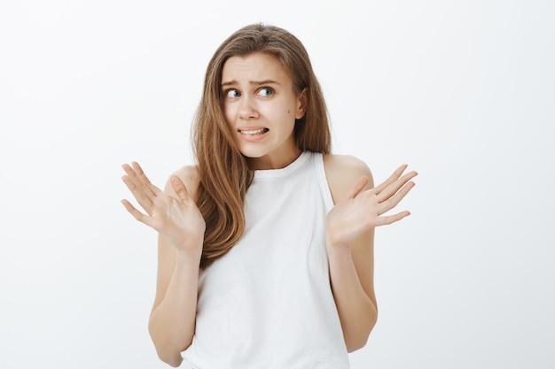 Close de uma garota indecisa e preocupada dando de ombros e levantando as mãos com uma careta