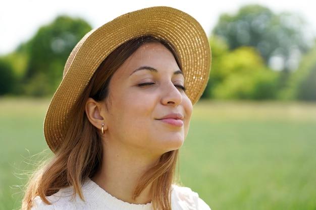 Close de uma garota respirando ar puro com os olhos fechados