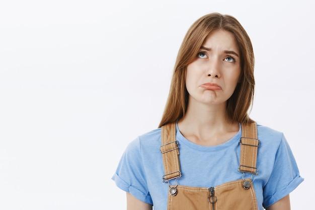 Close de uma garota triste, triste e chateada, olhando para cima e reclamando